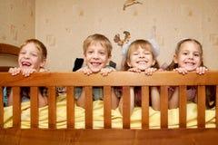 Uśmiechnięci dzieci, bracia i siostry kłama na łóżku, obraz royalty free