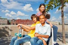 Uśmiechnięci dzieci siedzą na białych krzesłach w mieście Zdjęcia Royalty Free