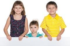 Uśmiechnięci dzieci trzymają białego prześcieradło papier zdjęcie royalty free