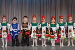 Uśmiechnięci dzieci w ludowym kostiumu wykonują na scenie zdjęcie stock