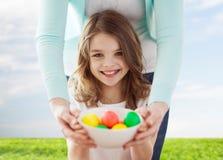 Uśmiechnięci dziewczyny i matki mienia barwioni jajka obraz stock