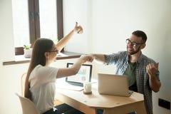 Uśmiechnięci freelancers daje pięść garbkowi i pokazuje aprobaty obraz stock