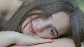 Uśmiechnięci kobiet kłamstwa outdoors otwierają oczu spojrzenia in camera, piękna dziewczyna w parku zbiory wideo