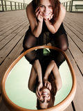 Uśmiechnięci kobiet spojrzenia przy odbiciem w lustrze Fotografia Royalty Free