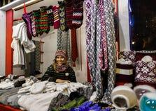 Uśmiechnięci kobieta buble grżą odzieżowego przy Ryskim boże narodzenie rynkiem Fotografia Stock