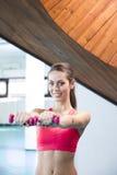 Uśmiechnięci kobieta udźwigu ciężary w gym Zdjęcia Stock