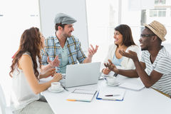 Uśmiechnięci koledzy oddziała wzajemnie laptop i używa Obrazy Stock
