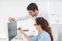 Uśmiechnięci koledzy pracuje na komputerze wpólnie Obrazy Royalty Free
