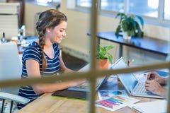 Uśmiechnięci koledzy pracuje wpólnie na laptopie Obrazy Royalty Free