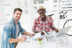 Uśmiechnięci koledzy pracuje z pastylką i laptopem Obrazy Stock