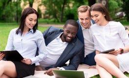 Uśmiechnięci koledzy siedzi na trawie obraz stock