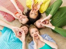 Uśmiechnięci ludzie łgarskiego puszka na podłogowym i krzyczącym Zdjęcia Royalty Free