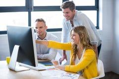 Uśmiechnięci ludzie biznesu dyskutuje nad komputerem zdjęcie stock