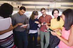 Uśmiechnięci ludzie biznesu dyskutuje w windzie zdjęcie royalty free