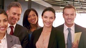 Uśmiechnięci ludzie biznesu pozuje wpólnie zdjęcie wideo