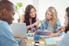 Uśmiechnięci ludzie biznesu pracuje przy biurkiem podczas gdy używać cyfrową pastylkę Fotografia Stock
