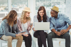 Uśmiechnięci ludzie biznesu używa technologię podczas gdy dyskutujący Obrazy Royalty Free
