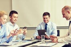 Uśmiechnięci ludzie biznesu z gadżetami w biurze zdjęcia stock