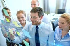 Uśmiechnięci ludzie biznesu z markierem i majcherami Fotografia Stock