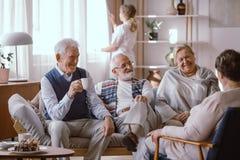 Uśmiechnięci ludzie opowiada wpólnie w karmiącym domu fotografia stock