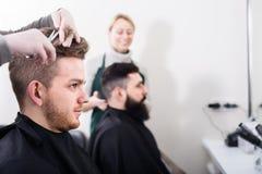 Uśmiechnięci mężczyzna klienci przy włosianym salonem fotografia royalty free