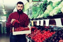 Uśmiechnięci męscy sprzedawca ofiary pomidory w sklepie Zdjęcia Stock