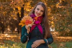 Uśmiechnięci młoda dziewczyna stojaki w jesieni Parkują i utrzymania wysuszeni liście w ręce Zdjęcie Royalty Free