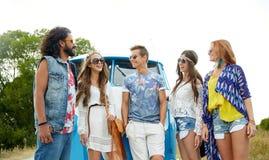 Uśmiechnięci młodzi hipisów przyjaciele nad furgonetka samochodem Obraz Stock