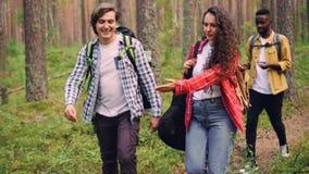 Uśmiechnięci młodzi ludzie przyjaciół chodzą w lesie z plecakami, atrakcyjna dziewczyna niesie gitarę, mężczyzna i kobiety są zbiory