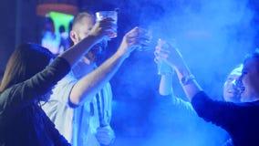 Uśmiechnięci młodzi ludzie w dymna podwyżka barwiących napojach w szkłach i robią grzance blisko zgłaszać przy klubem zdjęcie wideo