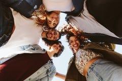 Uśmiechnięci młodzi przyjaciele tworzy skupisko fotografia royalty free