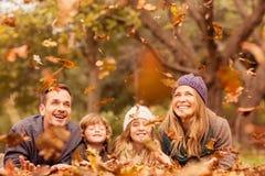Uśmiechnięci młodzi rodzinni miotanie liście wokoło zdjęcie stock