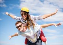Uśmiechnięci nastolatkowie w okularach przeciwsłonecznych ma zabawę outside Fotografia Stock