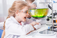 Uśmiechnięci nauczyciela i ucznia chemicy patrzeje kolbę z odczynnikiem Zdjęcie Stock