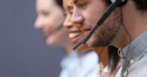 Uśmiechnięci obsług klienta kierownictwa opowiada na słuchawki przy biurkiem 4k zbiory wideo
