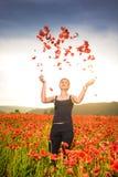 Uśmiechnięci piękni kobiety miotania płatki makowi kwiaty Obraz Stock