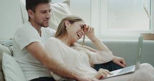 Uśmiechnięci piękni potomstwa dobierają się w ranku obsiadaniu na kanapie i dopatrywanie coś na notatniku, są oba zbiory