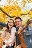 Uśmiechnięci potomstwa dobierają się outdoors w jesieni Zdjęcie Stock