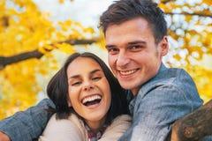 Uśmiechnięci potomstwa dobierają się outdoors w jesieni Zdjęcia Stock