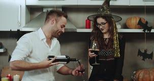 Uśmiechnięci potomstwa dobierają się przy Halloween przyjęciem, pije czerwone wino od szkieł przy kuchennymi zadziwiającymi dekor zdjęcie wideo