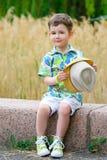 Uśmiechnięci potomstwa fasonują chłopiec trzyma jego kapelusz podczas gdy Obraz Stock