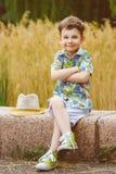 Uśmiechnięci potomstwa fasonują chłopiec z kapeluszem pozuje przy Zdjęcie Stock