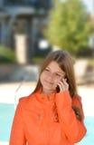 Uśmiechnięci potomstwa używać jej telefon komórkowego Zdjęcia Stock
