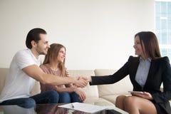 Uśmiechnięci potomstwo pary klienci trząść ręki z agentem, prawnik, m Obraz Royalty Free