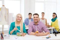 Uśmiechnięci projektanci mody ma lunch przy biurem Obrazy Royalty Free