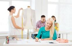 Uśmiechnięci projektanci mody pracuje w biurze Zdjęcie Royalty Free