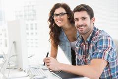 Uśmiechnięci projektantów koledzy używa digitizer wpólnie Obraz Royalty Free