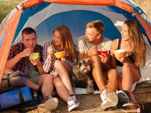 Uśmiechnięci przyjaciele je fastów food kluski na campingowej wycieczce Wycieczkowicze je na namiotowym tle Aktywnego urlopowy po Fotografia Royalty Free