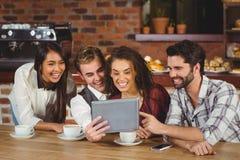 Uśmiechnięci przyjaciele patrzeje cyfrową pastylkę Obrazy Stock