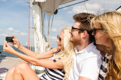 Uśmiechnięci przyjaciele siedzi na jachtu pokładzie zdjęcia royalty free